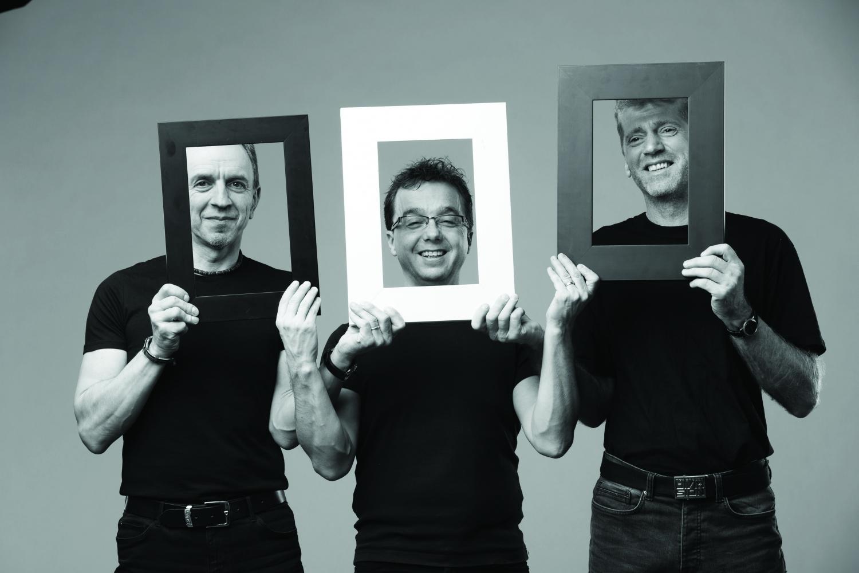 trzech mężczyzn na pozowanym zdjęciu – trzymają ramki na zdjęcia przy głowach