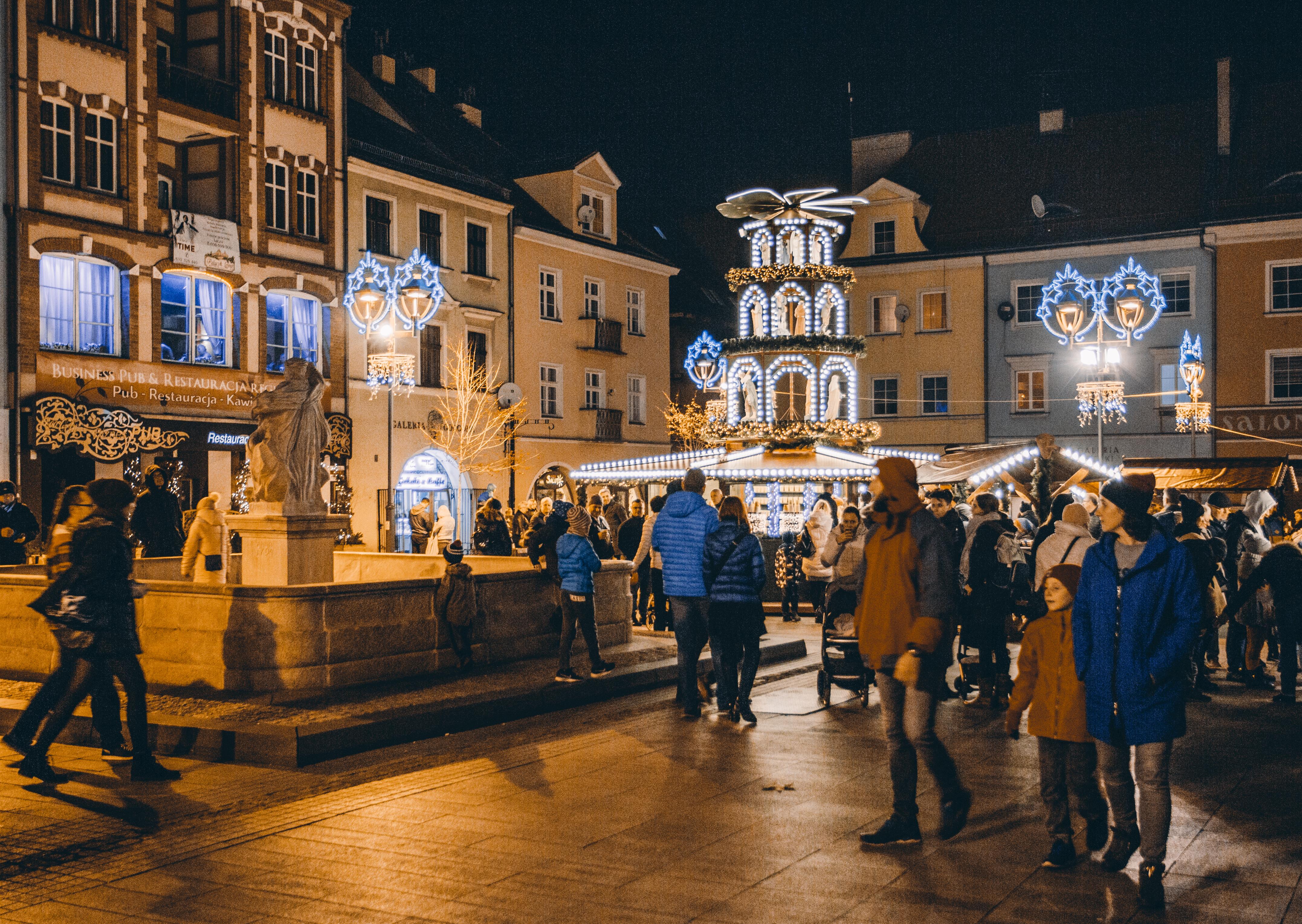 Rynek podczas jarmarku, wieczór, dużo ludzi, okolice fontanny z Neptunem