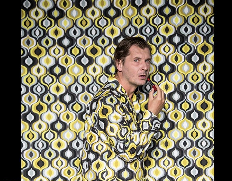 mężczyzna ze szminką na wzorzystym tle we wzorzystym ubraniu