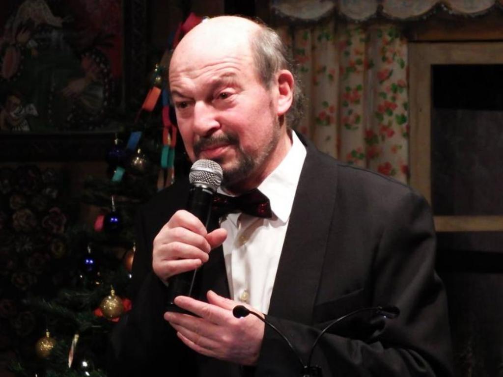 mężczyzna z mikrofonem stoi w pobliżu choinki