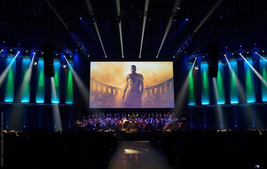 """koncert na wielkiej sali z wyśiwetloną sceną z filmu """"Gladiator"""" na ekranie"""