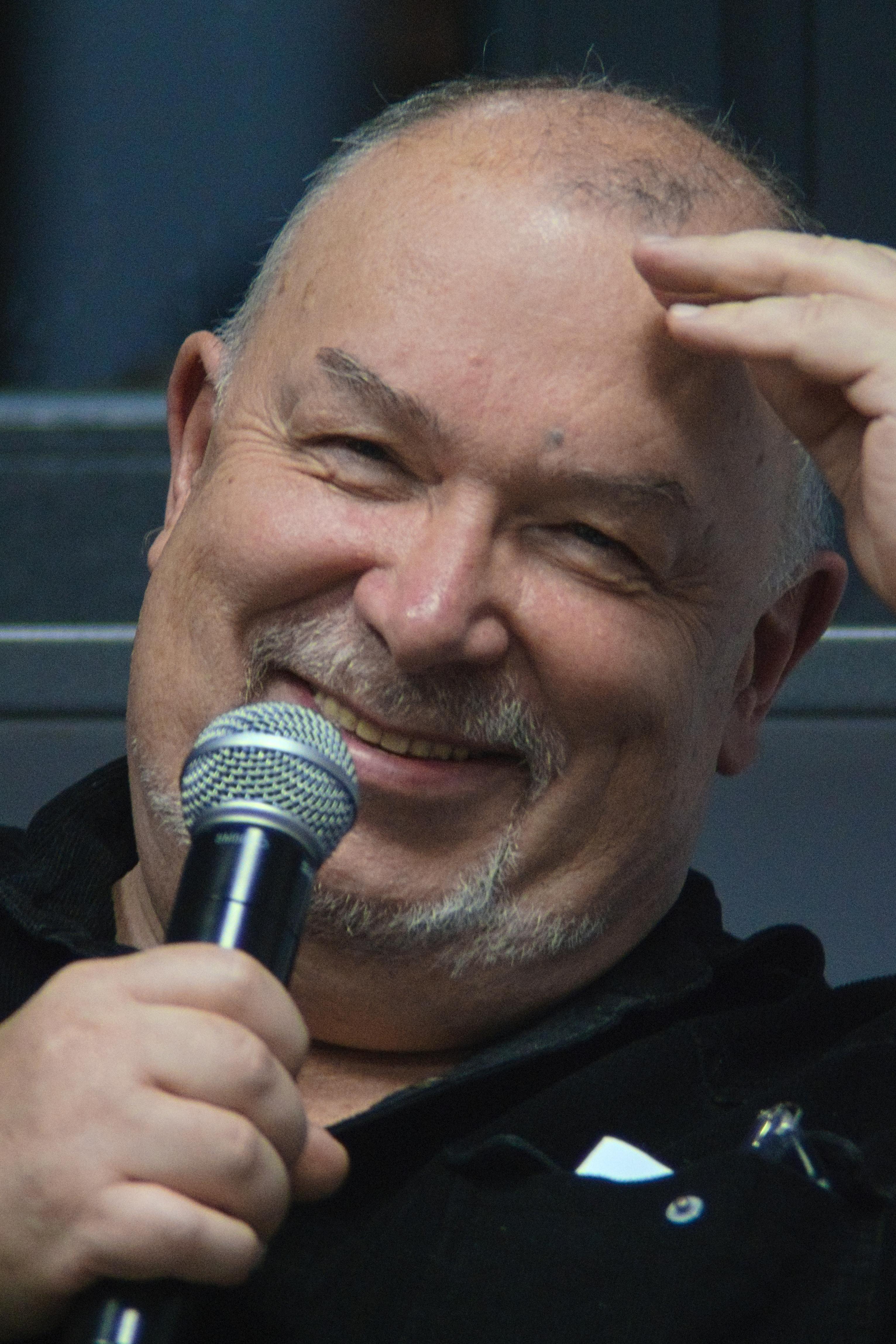 uśmiechnięty mężczyzna trzyma mikrofon