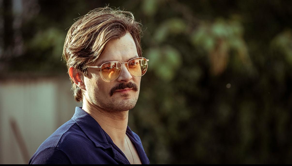 Dawid Ogrodnik w fryzurze z epoki i okularach, jako Najmrodzki