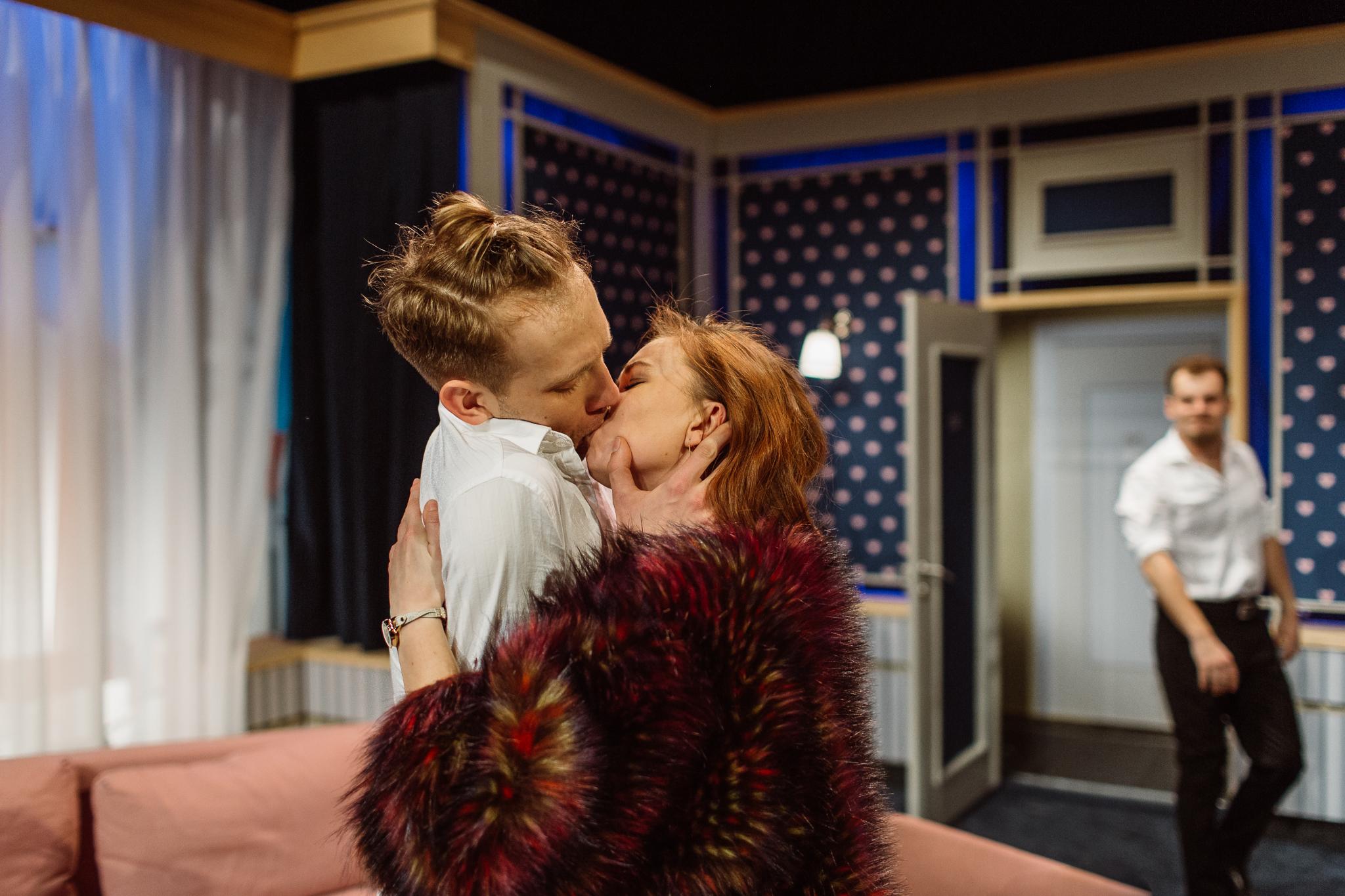 aktorzy na scenie, dwie osoby na peirwszym planie całują się, mężczyzna na drugim planie stoi w drzwiach